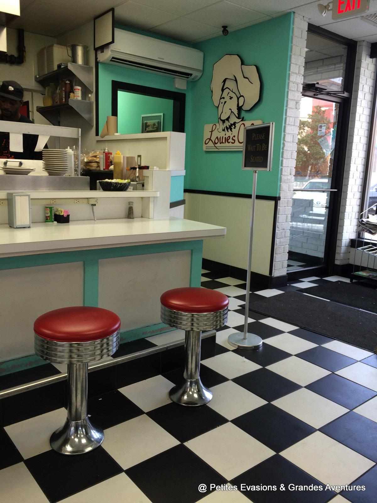 Intérieur d'un restaurant avec carrelage blanc et noir, tabourets rouges et murs turquoises